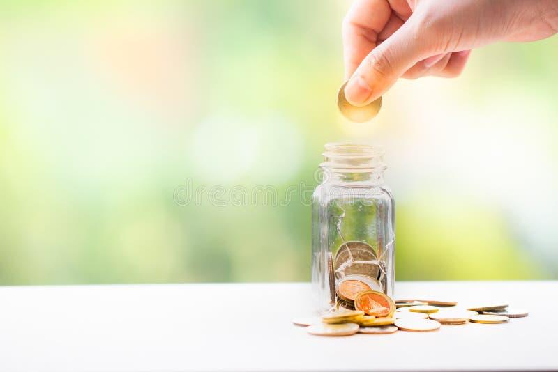 La mano della donna ha messo la moneta in un barattolo risparmio dei soldi Concetto di investimento immagine stock libera da diritti