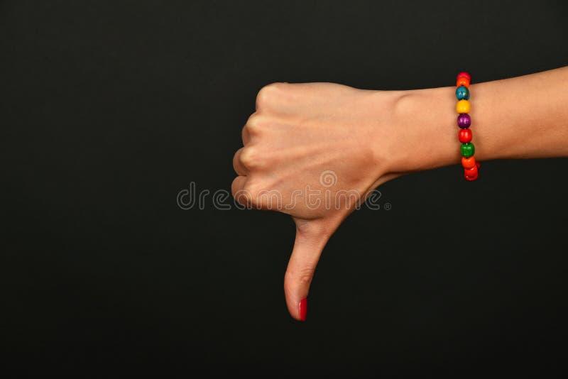La mano della donna mostra che il pollice giù gesture sopra il nero immagine stock libera da diritti
