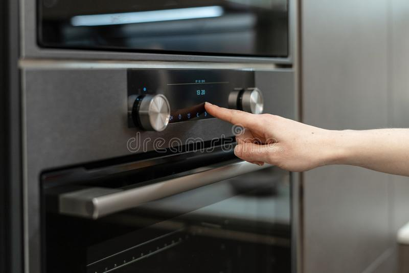 La mano della donna sceglie il programma sul forno incorporato del pannello di controllo elettronico fotografia stock