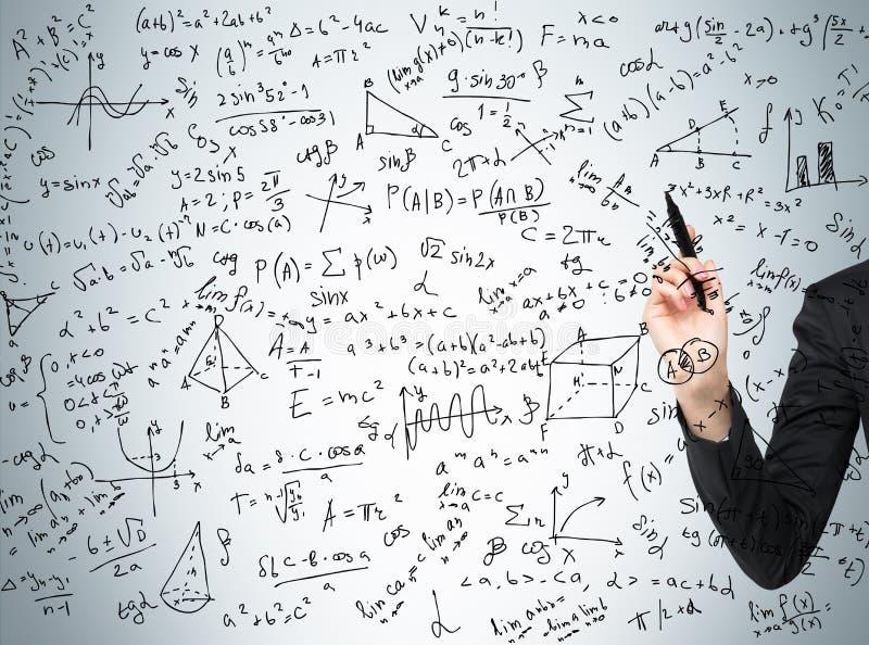 La mano della donna sta precisando i calcoli complicati di per la matematica fotografia stock