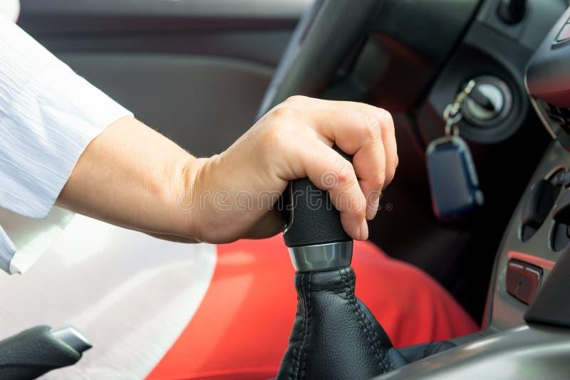 La mano della donna tenendo la leva dello spostamento in un'automobile fotografia stock