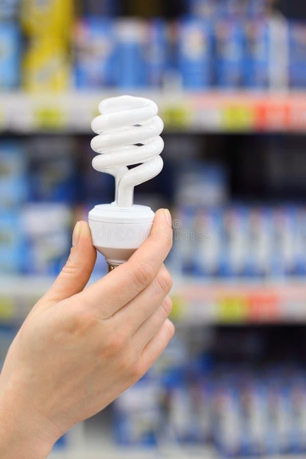 La mano della donna tiene la lampada bianca in negozio immagini stock