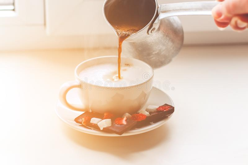 La mano della donna versa il caffè fragrante in una tazza fotografia stock