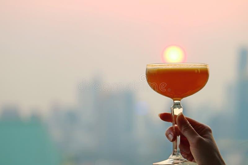 La mano della femmina che tiene un vetro di cocktail contro il tramonto con i grattacieli confusi in contesto immagini stock libere da diritti