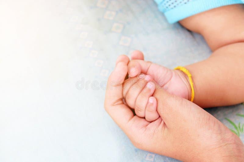 La mano della madre culla la mano di un bambino fotografia stock libera da diritti