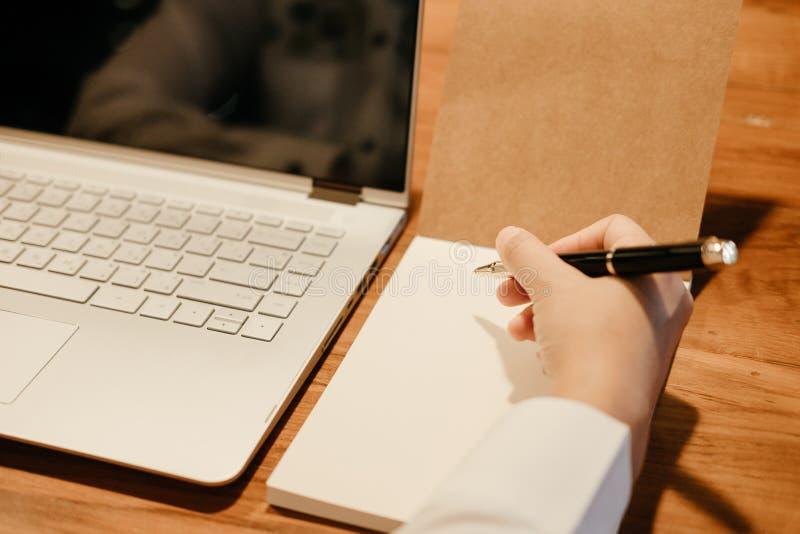 la mano della penna della tenuta dell'uomo d'affari scrive sul taccuino noteboo del computer fotografie stock