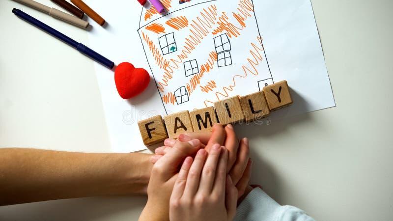 La mano della persona adulta, parola della tenuta del bambino della famiglia ha fatto dai cubi sull'immagine della casa fotografia stock libera da diritti