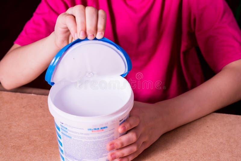 La mano della ragazza apre una latta di pittura acrilica bianca fotografia stock
