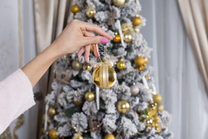 La mano della ragazza che giudica Natale gioca, palla, albero con gli ornamenti fotografia stock