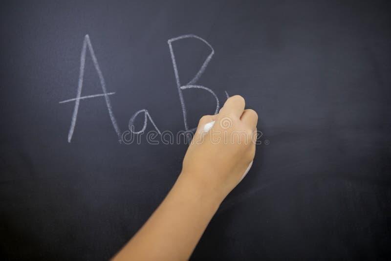 La mano della scolara scrive le lettere dell'alfabeto fotografia stock