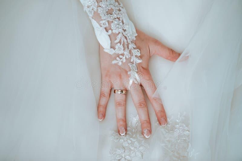 La mano della sposa sul suo vestito da sposa con l'anello fotografie stock libere da diritti
