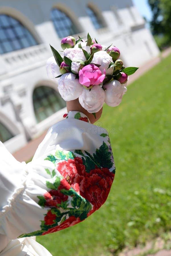 La mano della sposa in una camicia ricamata che tiene un mazzo di nozze delle peonie fotografie stock
