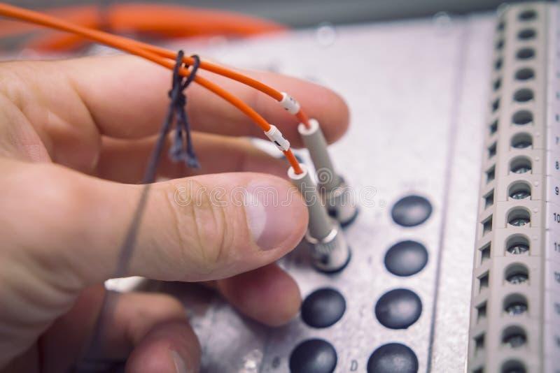 La mano delle inserzioni dell'ingegnere e collega il cavo di toppa a fibra ottica alla fine industriale del dispositivo di comuni fotografia stock libera da diritti