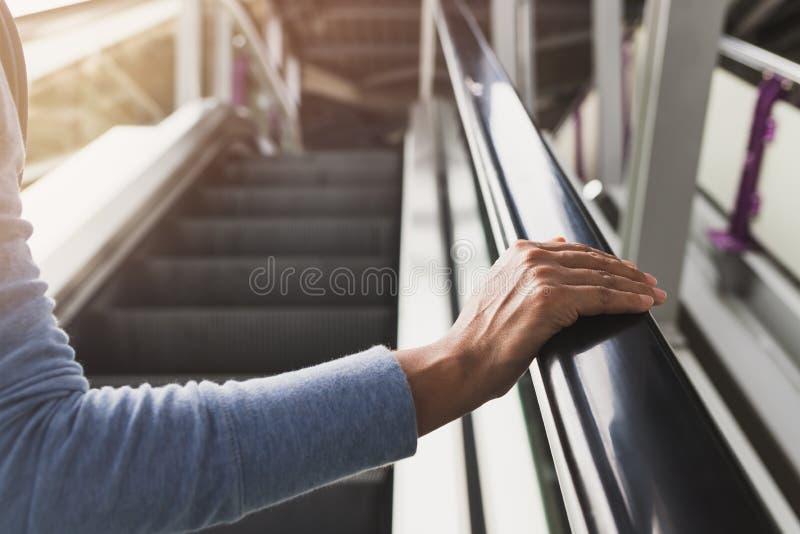 La mano derecha de la mujer en la barandilla de la escalera móvil imagenes de archivo