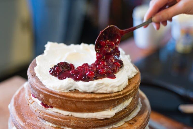 La mano desnuda de la torta toping la fresa poner crema azotada de las bayas cocinó casarse del cumpleaños hecho en casa fotografía de archivo libre de regalías