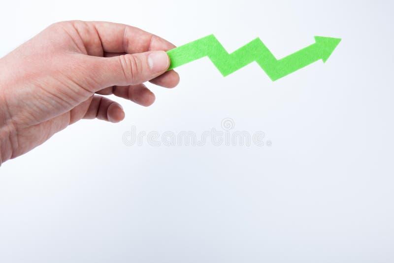 La mano detiene la flecha verde, como símbolo del éxito Espacio vac?o para el texto foto de archivo