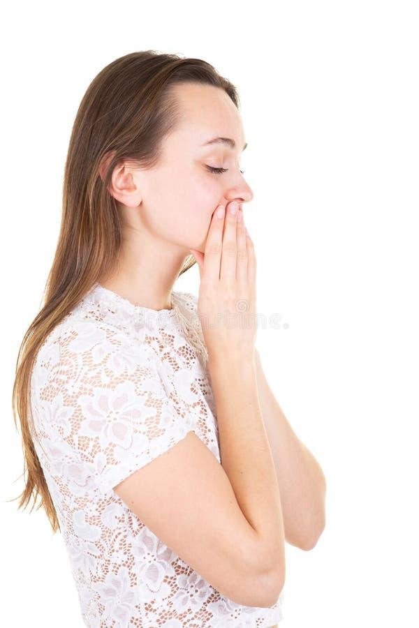 La mano di profilo della giovane donna sulla bocca ha chiuso gli occhi che bisbigliano sul fondo bianco fotografia stock libera da diritti