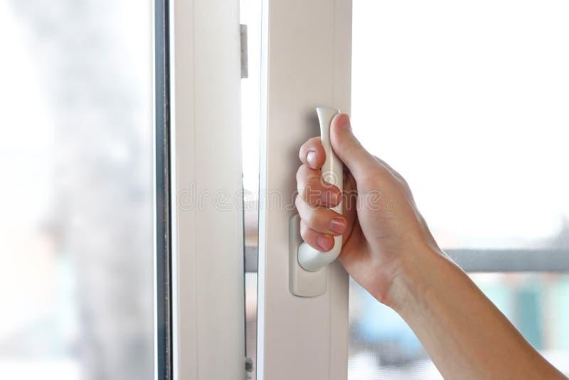 La mano di un uomo apre una finestra di plastica bianca Fine in su fotografia stock libera da diritti