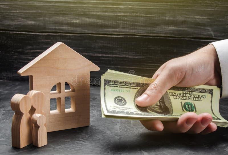 La mano di un uomo d'affari allunga un batuffolo di soldi alle figure della famiglia vicino alla casa di legno Fornitura del mutu fotografie stock libere da diritti