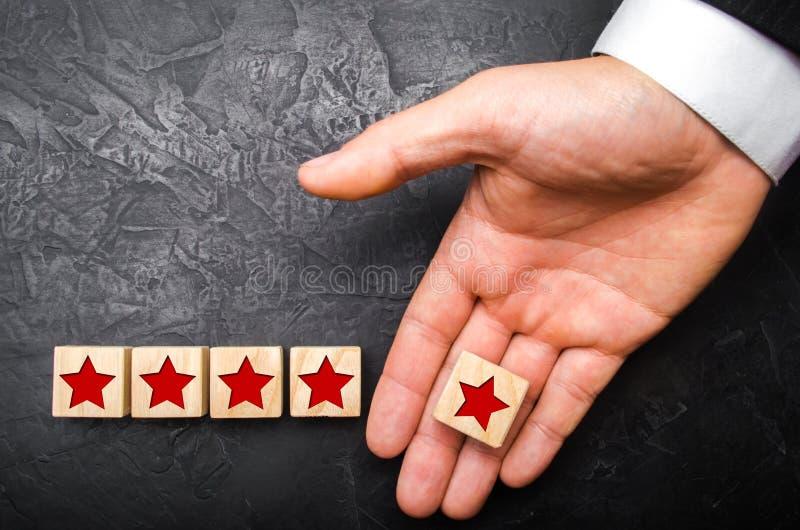 La mano di un uomo d'affari allunga la quinta stella Il concetto di assegnazione della stella nuova e di sollevare lo stato, pres fotografie stock libere da diritti