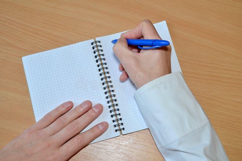 La mano di un uomo in una camicia bianca scrive il testo con una penna blu in un taccuino con una coclea su una tavola di legno,  immagini stock