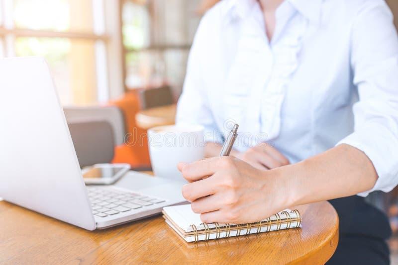 La mano di una donna di affari sta lavorando ad un computer e ad una scrittura immagini stock