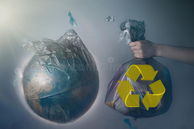 La mano di una donna tiene una borsa di immondizia accanto al globo di pianeta Terra Concetto di ecologia e di protezione dell'am fotografia stock libera da diritti