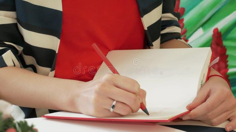 La mano di una giovane donna in un vestito a strisce prende le note con una matita in un blocco note rosso immagini stock