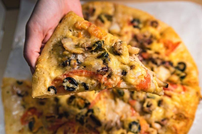 La mano di vista superiore tiene la fetta di pizza fotografia stock