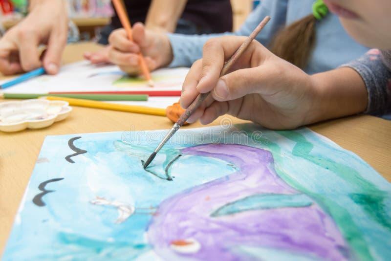 La mano dibuja un dibujo en una escuela del dibujo foto de archivo