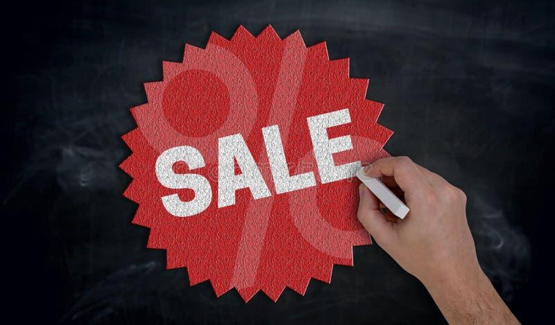 La mano dipinge con la vendita del gesso sul concetto della lavagna fotografia stock libera da diritti