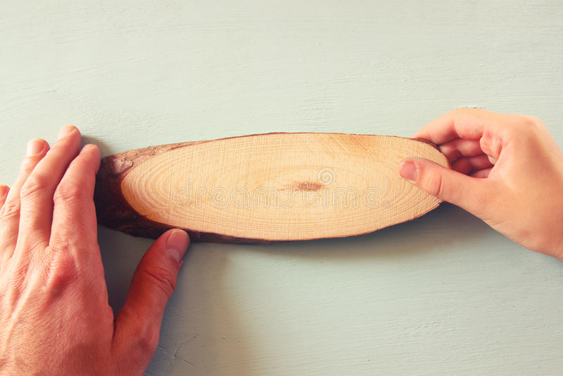 La mano ed il bambino maschii passano la mostra del segno in bianco di legno Stanza per testo fotografie stock