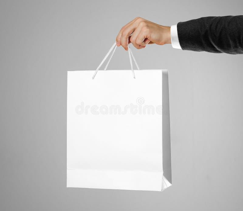 La mano en la camisa blanca y la chaqueta negra sostiene un bolso blanco del regalo fotos de archivo