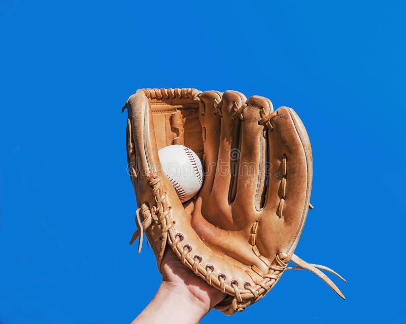 La mano en el guante para el juego de béisbol alcanzó gran popularidad una bola blanca de cuero imagen de archivo libre de regalías