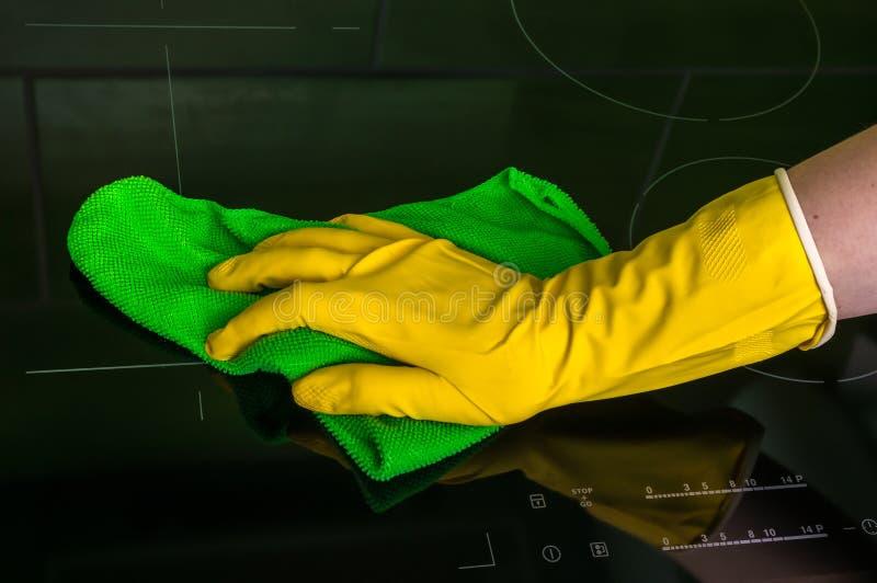 La mano en guante con el trapo verde está limpiando las placas de la inducción fotos de archivo libres de regalías