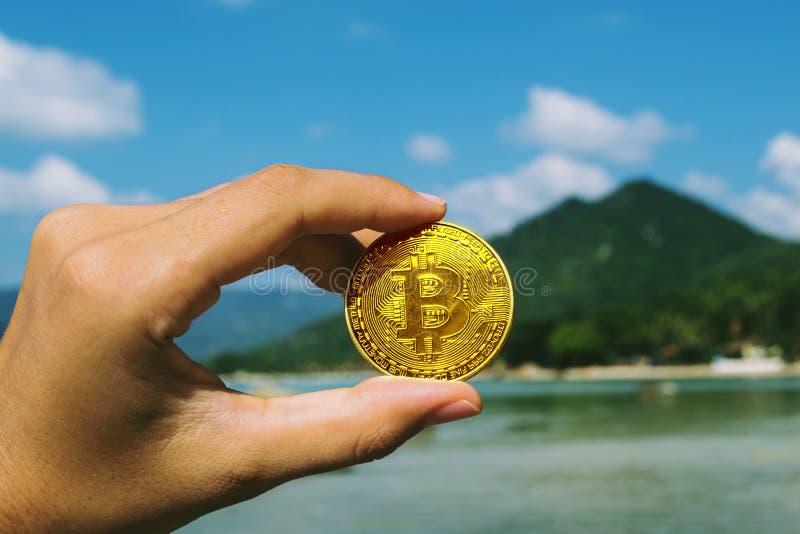 La mano es color oro de Bitcoin del control imagenes de archivo