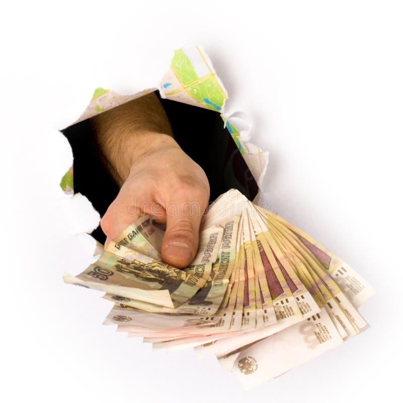 La mano es llena de dinero ruso, perforando un agujero en el papel imagen de archivo