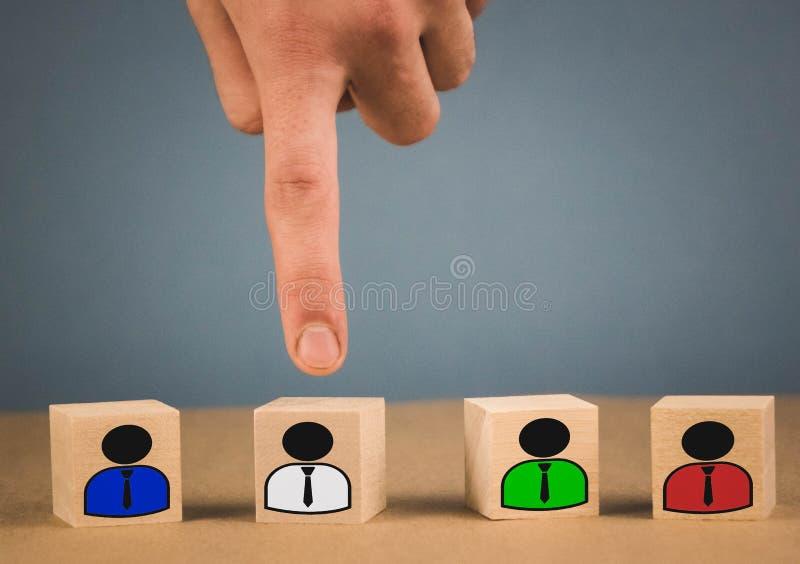 la mano escoge un cubo de madera con un hombre en una camisa blanca foto de archivo