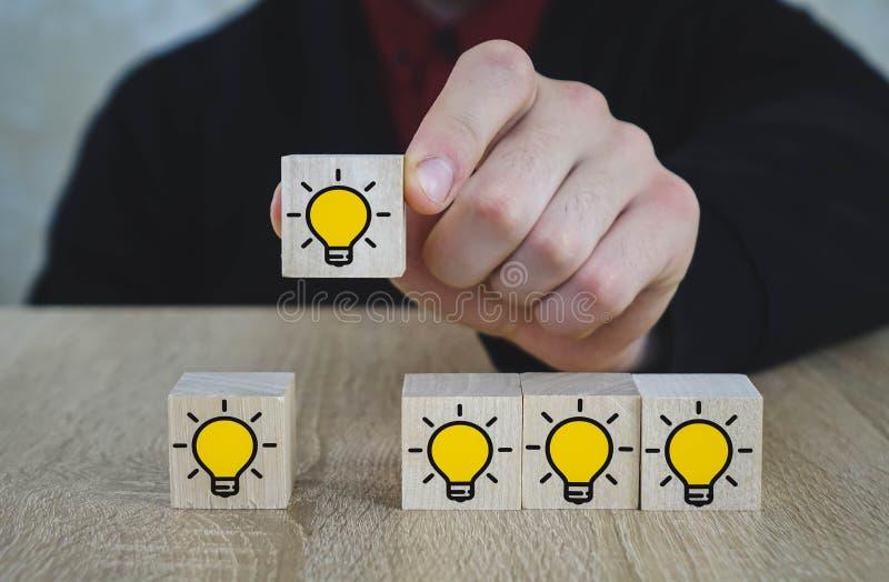 La mano escogió los cubos de madera con el símbolo del bulbo de la luz ámbar en la tabla de madera Nuevos idea, conceptos de la i foto de archivo