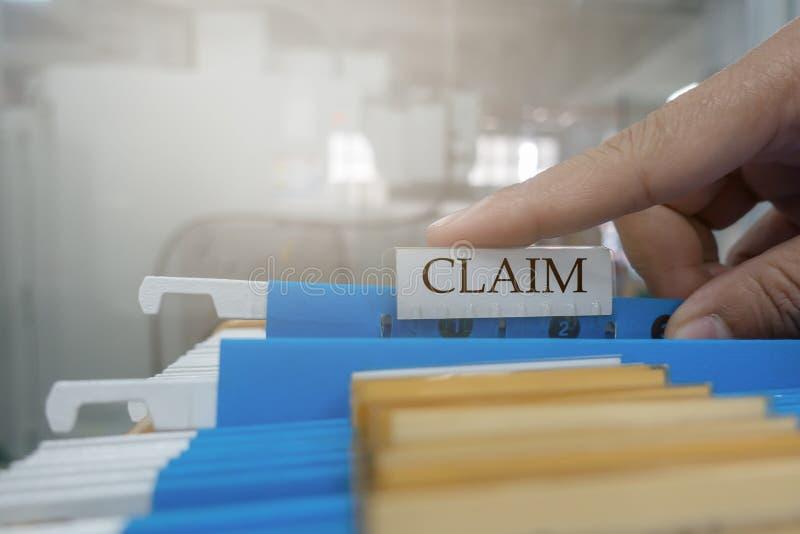 La mano est? cogiendo el documento de la demanda en el fichero para el cliente a la compa??a de seguros Concepto del seguro fotografía de archivo