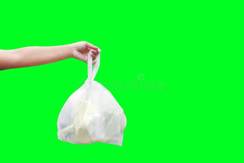 La mano está llevando los bolsos de basura plásticos inútiles aislados en el fondo de pantalla verde, mano que sostiene los bolso fotos de archivo libres de regalías