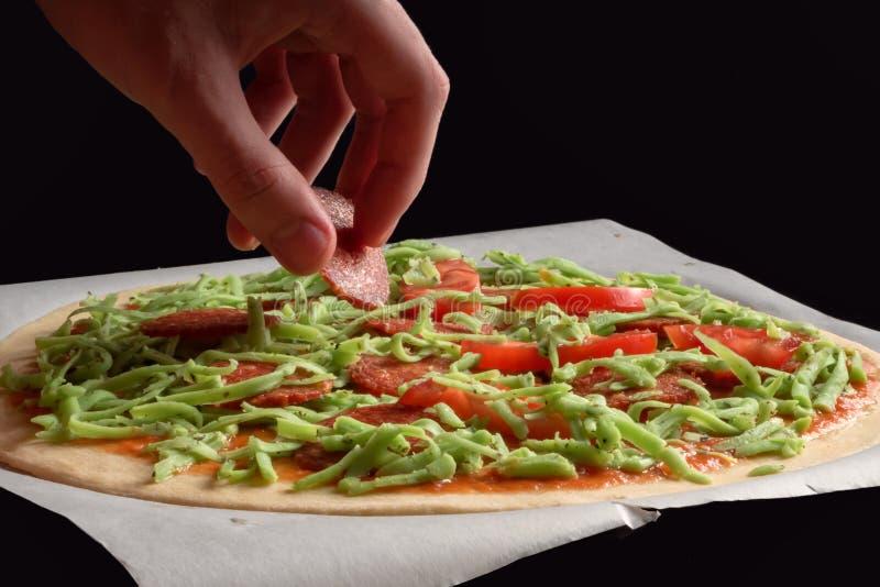 La mano está poniendo el salami en base verde de la pizza de queso fotos de archivo
