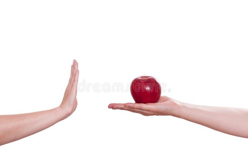 La mano está rechazando una manzana imagen de archivo libre de regalías