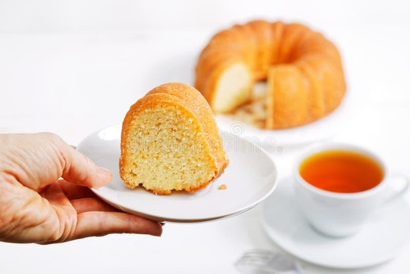La mano está sosteniendo un platillo con un pedazo de torta del limón imagen de archivo libre de regalías