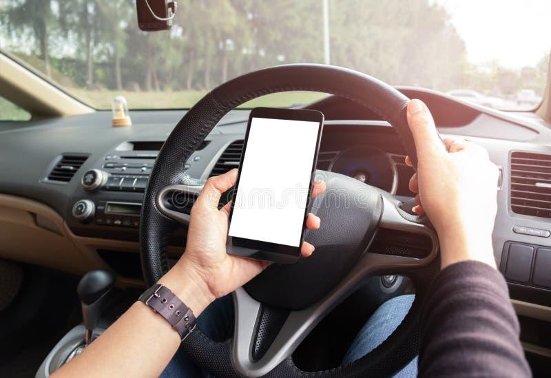 La mano está sosteniendo un teléfono del tacto con la pantalla aislada en el coche fotografía de archivo