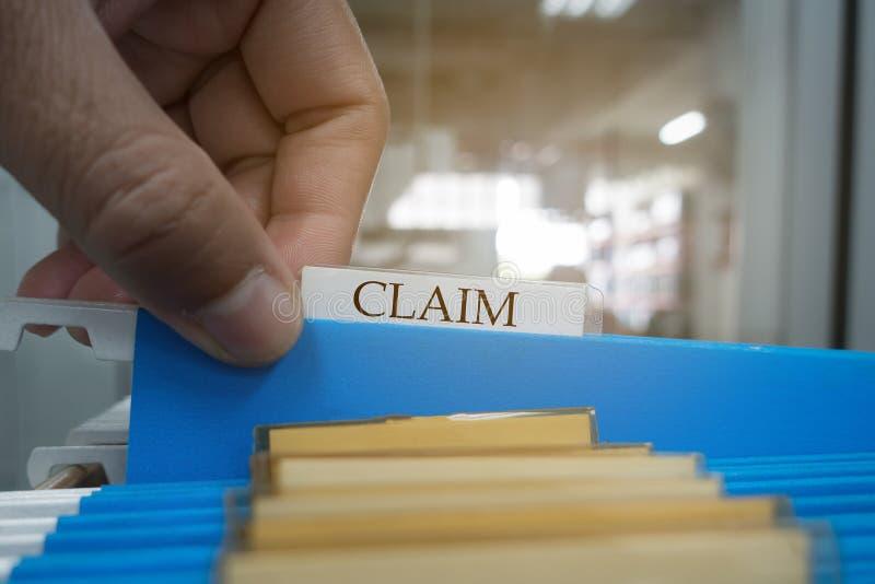 La mano est? cogiendo el documento de la demanda en el fichero para el cliente a la compa??a de seguros Concepto del seguro fotos de archivo