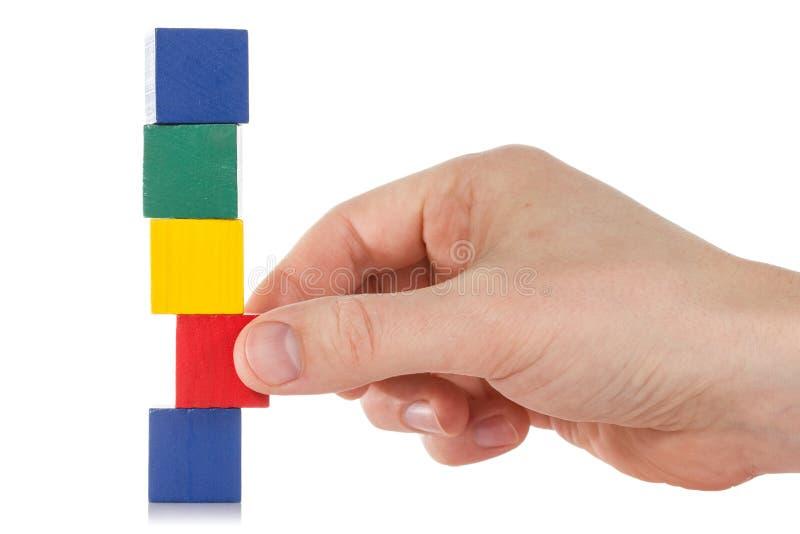 La mano establece un cubo de madera imagenes de archivo