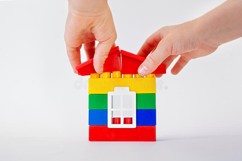 La mano establece un tejado del juguete en los cubos plásticos dé poner un tejado para componer una casa en el fondo blanco Const imagenes de archivo