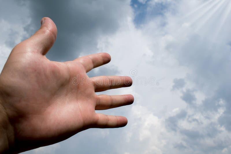 La mano estiró a un cielo llenado de las nubes oscuras conveniente para la cubierta de libro, ejemplo de la tarjeta, presentación imagenes de archivo