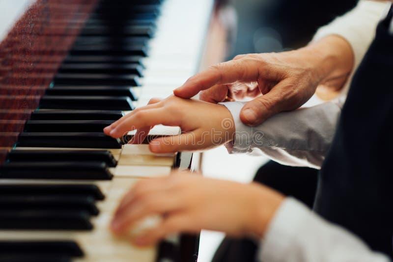 La mano experimentada del viejo profesor de música ayuda al alumno del niño fotos de archivo libres de regalías